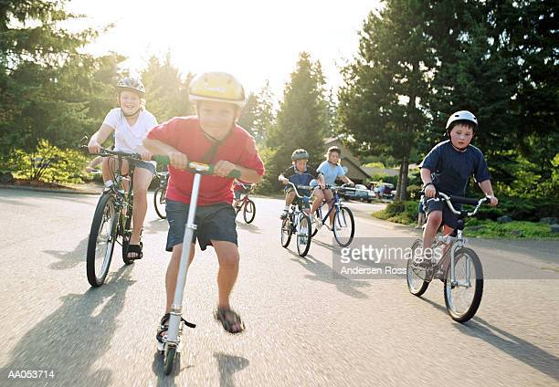 Group of children (5-10) riding push scooters and bicycles