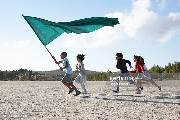 Group of children (9-12) running on beach with flag