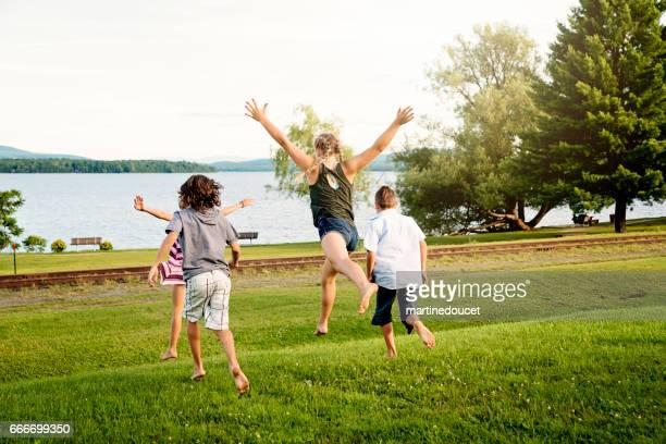 Group of children running toward lake in summer.
