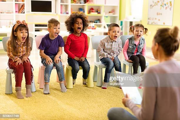 grupo de crianças gritam durante histórias no jardim da infância. - narração de histórias - fotografias e filmes do acervo
