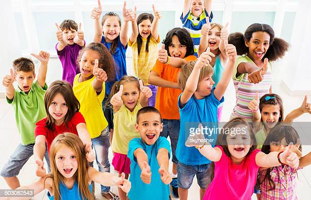 Group of children showing thumbs up.