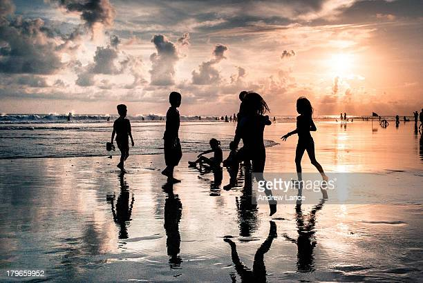 Group of children silhouetted against the sun, play between the waves and sand on Legian beach, Bali, Indonesia.