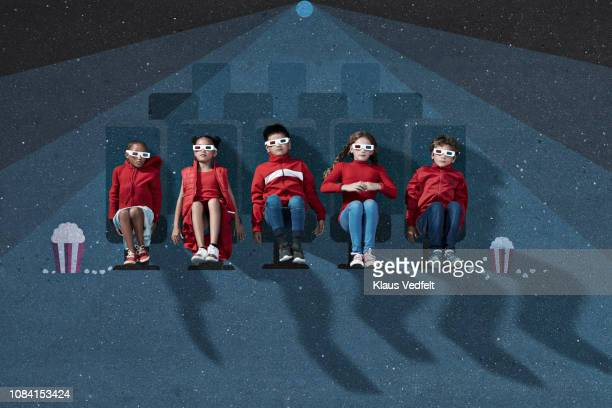 Group of children sitting in imaginary cinema dressed in red, wearing 3-D glasses