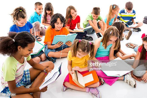 Group of children sitting on floor and learning.