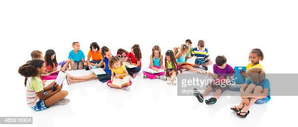 Group of children sitting on floor and studying together.