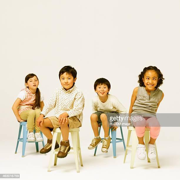 Group Of Children Sitting On Stool