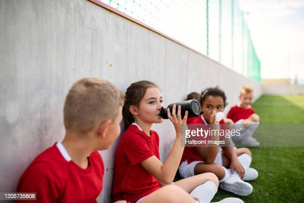 a group of children sitting outdoors on football pitch, resting. - clubvoetbal stockfoto's en -beelden