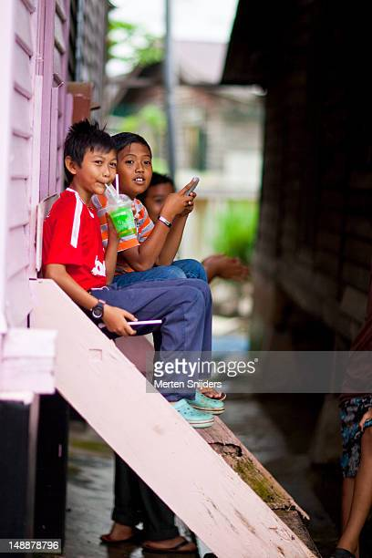 group of children sitting outside house in chow kit. - merten snijders stock pictures, royalty-free photos & images