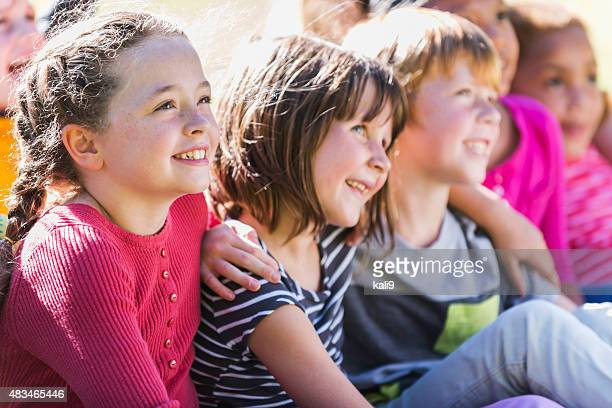 Group of children sitting together outdoors, smiling