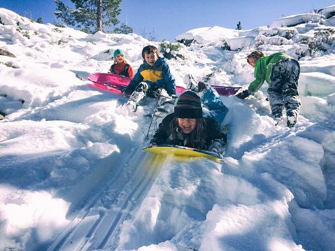 Group of children sledding together 641160216
