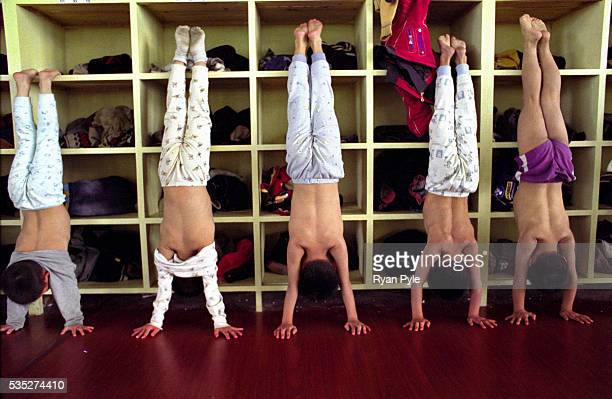 A group of children stand on their hands at the Li Xiaoshuang Gymnastics School in Xiantao China Li Xiaoshuang was a sucessful Chinese gymnast who...