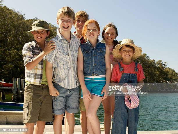 Group of children (7-13) standing by lake, smiling, portrait
