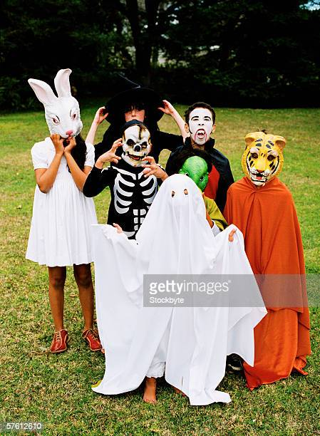 group of children (6-10) standing in a lawn wearing halloween costumes - rabbit mask stock pictures, royalty-free photos & images