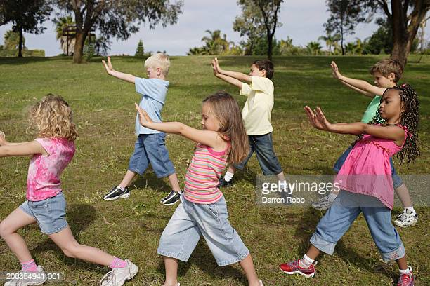 group of children (6-7 years) standing in park, arms out, side view - 6 7 years stock pictures, royalty-free photos & images