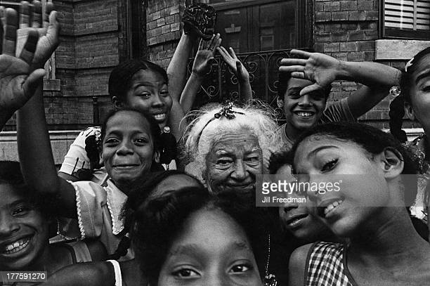 A group of children surrounds an elderly woman in the South Bronx New York City 1976