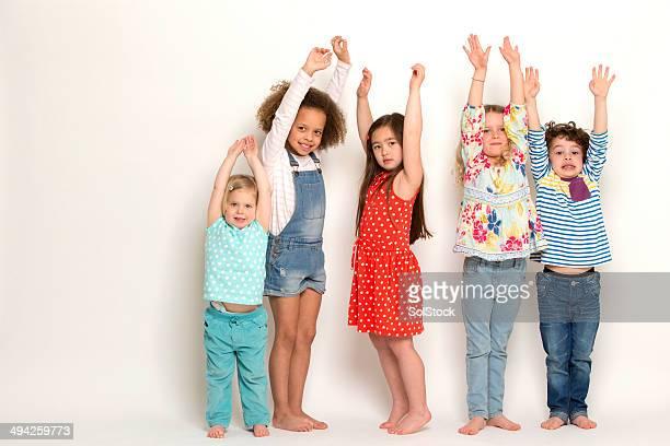 Gruppo di bambini con le braccia sollevate