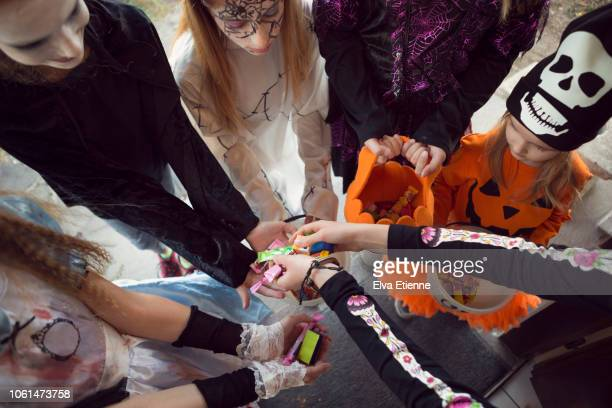 group of children trick or treating for sweets on halloween - halloween candy stock photos and pictures