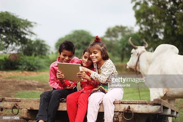 group of children using digital tablet - innocence stock pictures, royalty-free photos & images