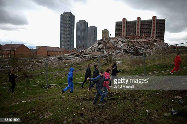 A group of children walk past a thirty story tower block at Birnie Court after it was demolished on May 5 2013 in Glasgow Scotland This was the...