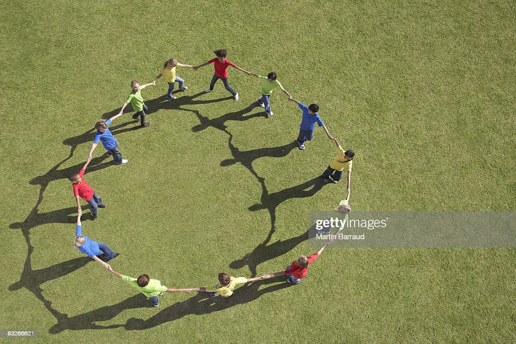 Group of children walking in circle holding hands : Stock Photo