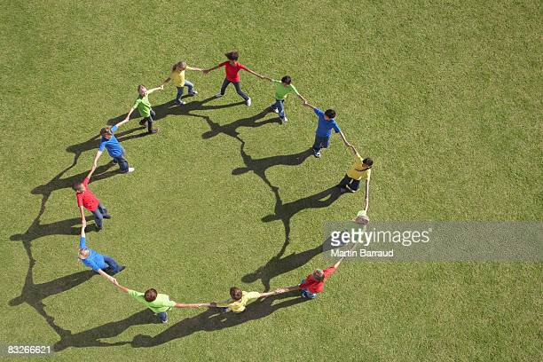 Group of children walking in circle holding hands