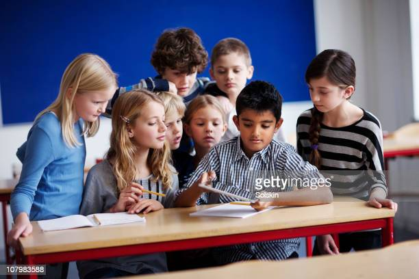 Group of children watching boy with tablet compute