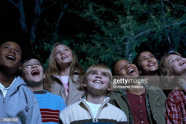Group of children (8-9, 10-11, 12-13) watching film in garden at night, laughing