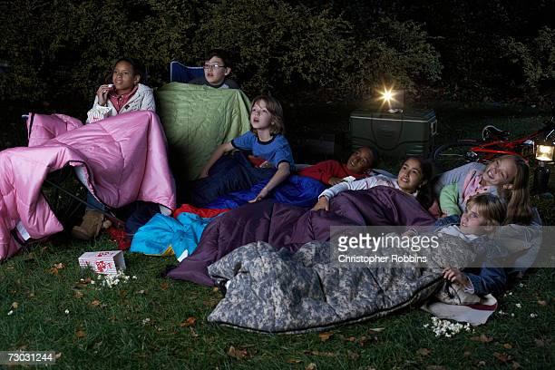 Group of children (8-9, 10-11, 12-13) watching film in garden at night
