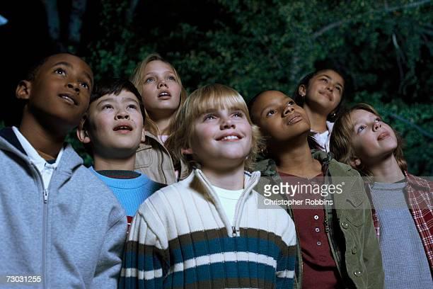 Group of children (8-9, 10-11, 12-13) watching film in garden at night, smiling