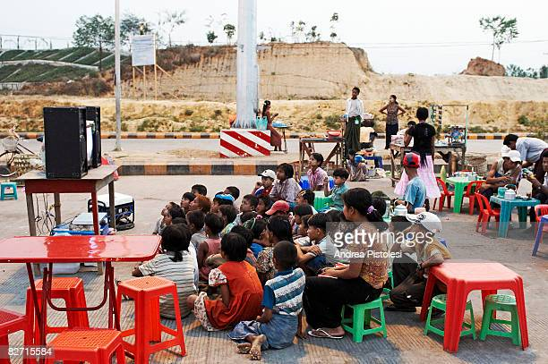group of children watching tv outdoors, myanmar - naypyidaw stock pictures, royalty-free photos & images