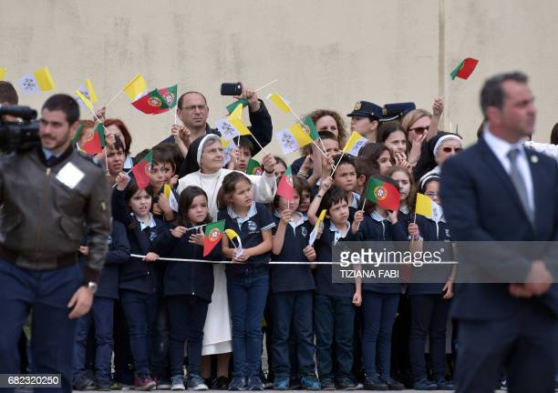 A group of children wave Portuguese and Vatican flags as they wait for Pope Francis at the Monte Real Air Base central Portugal prior his visit to...