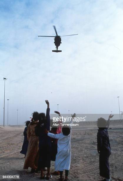 A group of children wave up as an American military helicopter flies overhead during the Gulf War Iraq 1991
