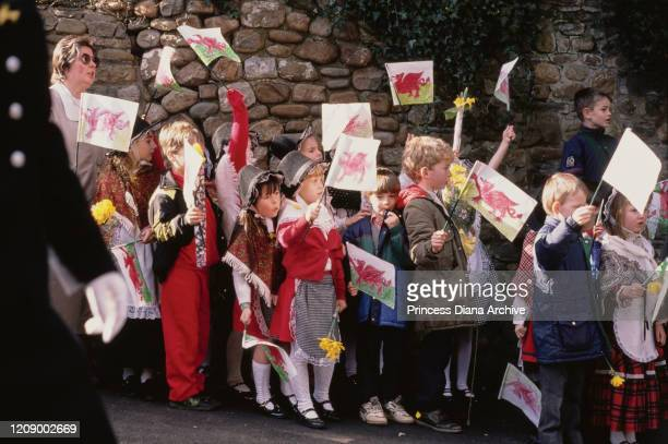 A group of children waving Welsh flags in Cardiff Wales during a visit by Prince Charles and Diana Princess of Wales for their son William's first...