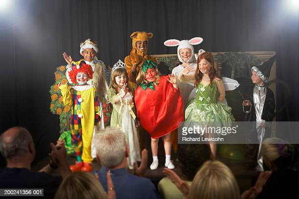 Group of children (11-14) wearing costumes, waving on stage