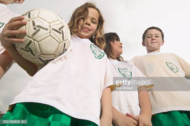 Group of children (6-11) wearing soccer uniforms, low angle view