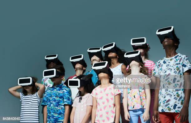 group of children wearing virtual reality headsets - futuristisch stockfoto's en -beelden
