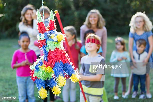 group of children with boy hitting pinata - cinco de mayo stock photos and pictures