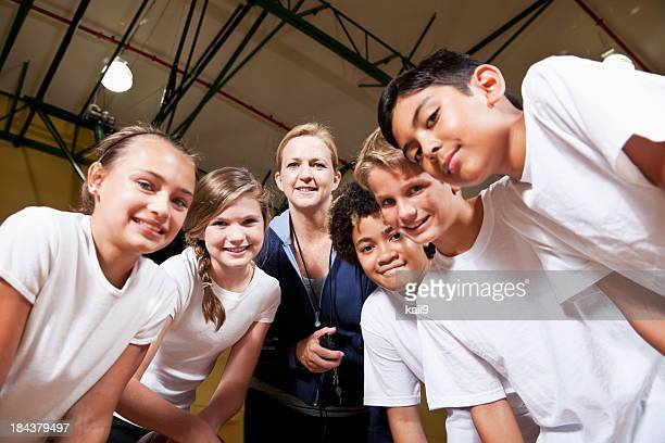 Group of children with coach in school gym