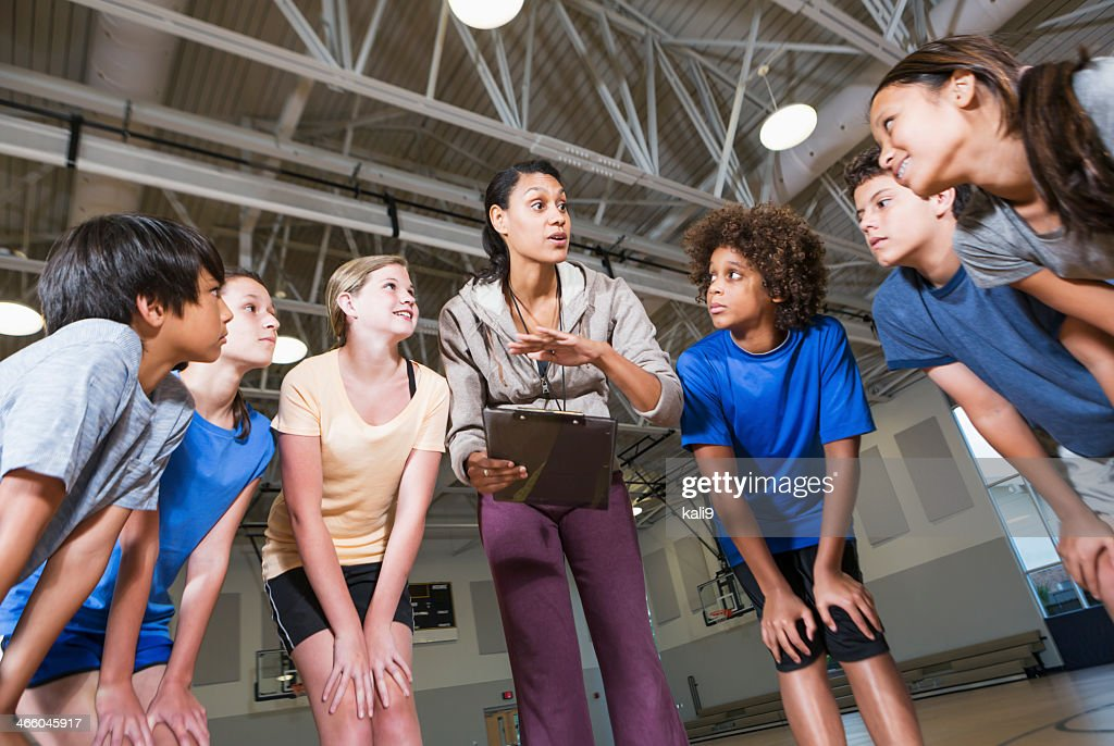 Group of children with coach in school gym : Stock Photo