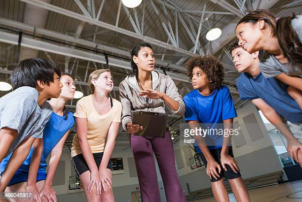 group of children with coach in school gym - 13 year old black girl stock photos and pictures