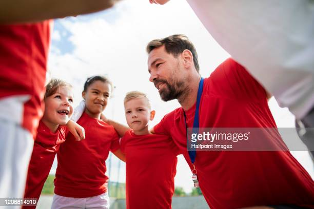 a group of children with coach standing in circle outdoors on football pitch. - voetbal teamsport stockfoto's en -beelden
