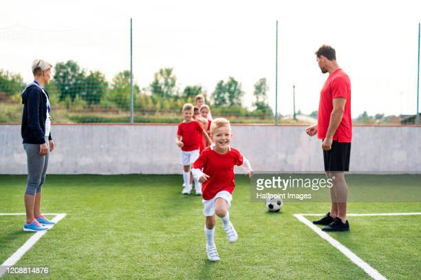 a group of children with coach training on football pitch. - clubvoetbal stockfoto's en -beelden