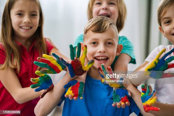 group of children with colored hands - 4 girls finger painting stock pictures, royalty-free photos & images