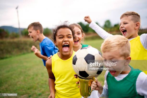 a group of children with cup prize standing outdoors on football pitch. - sports activity stock pictures, royalty-free photos & images
