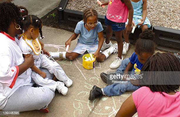 group of children with disabilities having a great time with sidewalk art! - cerebrum stock photos and pictures