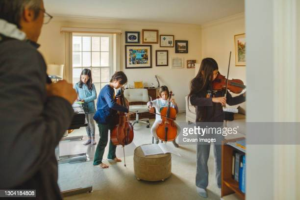 a group of children with stringed instruments play as father watches - performance group stock pictures, royalty-free photos & images