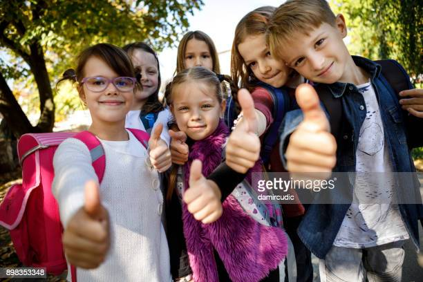 gruppe von kindern mit daumen hoch zeichen - grundschule stock-fotos und bilder