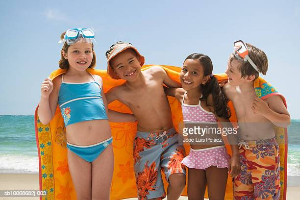 Group of children (6-9) wrapped in towel standing on beach, smiling,