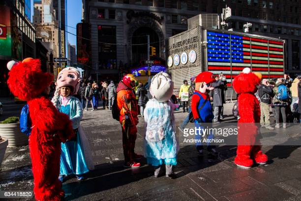 A group of childrens costume characters including Elmo from Sesame Street and Elsa from Frozen stand waiting to interact with tourists in Times...