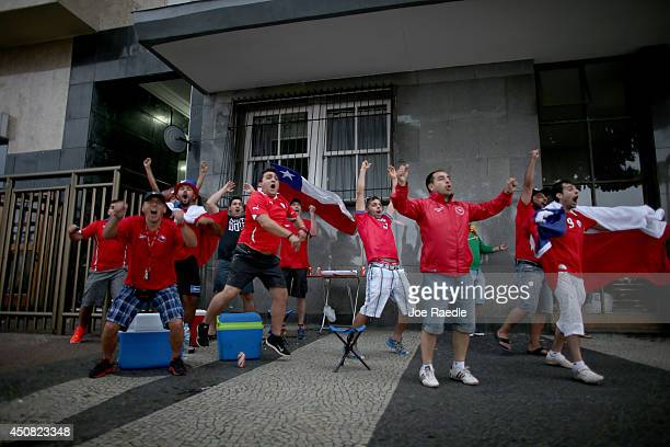 A group of Chilean soccer team fans react as their team scores their first goal during play against Spain while watching it on the screen setup at...